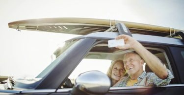 Elderly man and woman photographing self in car --- Image by © Tim Hale Photography/Corbis