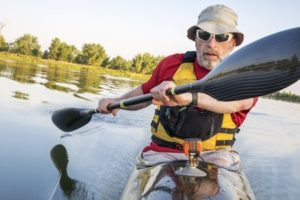 30680546 - senior male is paddling a fast racing sea kayak with a wing paddle on a calm lake, fort collins, colorado