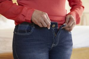 33519173 - close up of overweight woman trying to fasten trousers